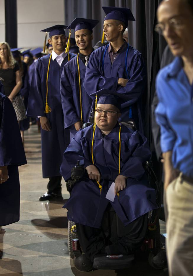Lifelong friends Colton Shrum, Darius Martin and D'Aron Martin line up with other students at the Cashman Center  for their Odyssey Charter School graduation on Tuesday, June, 3, 2014.