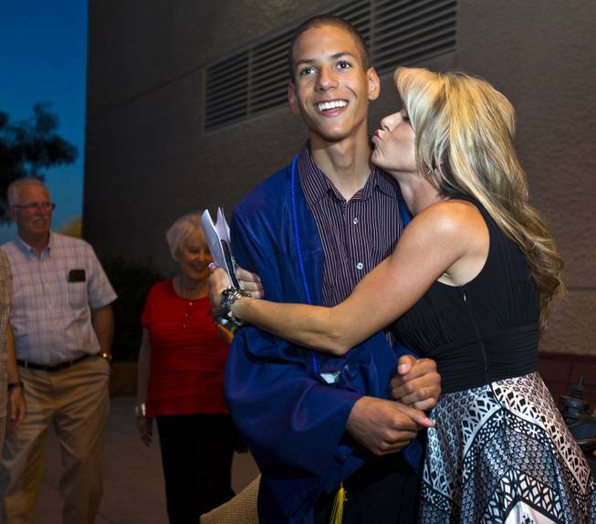 Darius Martin is kissed by Shelly Shrum as they joke around following the Odyssey Charter School graduation at the Cashman Center on Tuesday, June, 3, 2014.