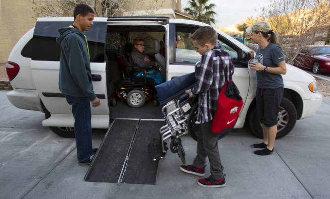 Darius Martin looks on as Hayden Shrum helps to load up his brother Colton with their mother Shelly standing by, preparing to leave for class at Odyssey Charter School on Tuesday, January, 28, 2014.