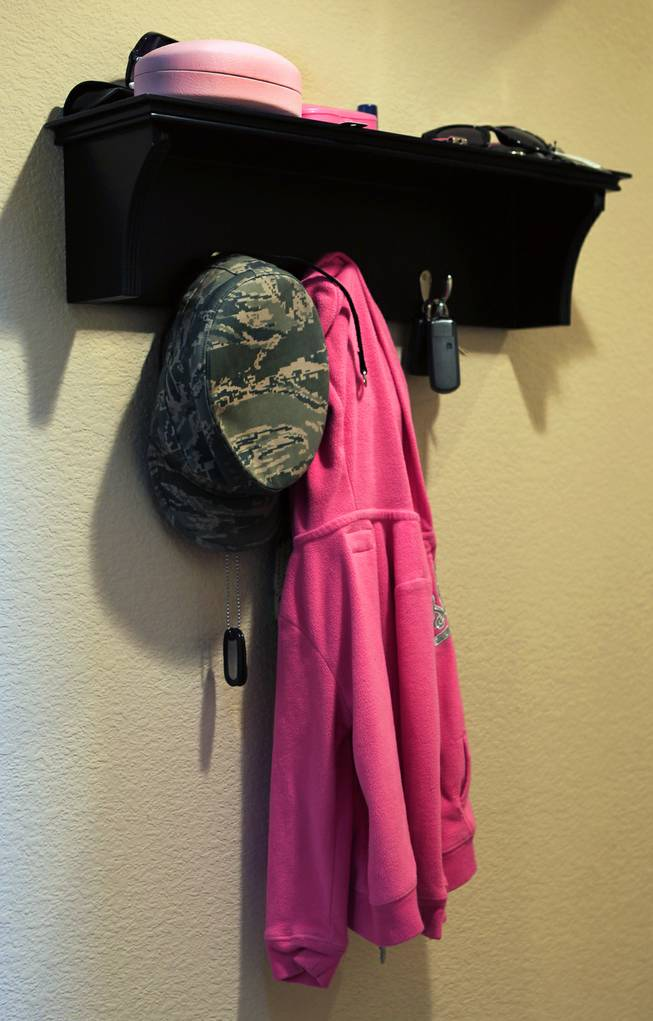 A hat and dog tags belonging to TSGT Rommel Delmundo, currently stationed at Nellis AFB, hang on a small shelf with other family possessions as they ready for another military move Monday, June 16, 2014.