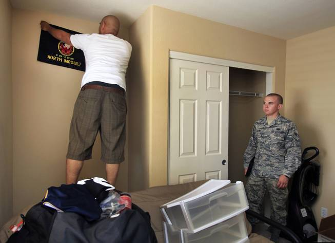 TSGT Rommel Delmundo, currently stationed at Nellis AFB, takes down a unit flag from his bedroom as he and his family ready for another military move Monday, June 16, 2014.  A1C Jake Carter with Nellis AFB public affairs assists to ensure things go smoothly.