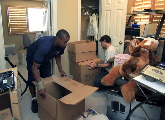 Eric Crockett and Jeff Lenning with Southern Nevada Movers work to pack up the household goods of the Delmundo family Monday, June 16, 2014.