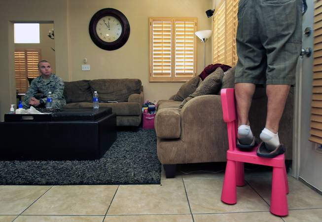 TSGT Rommel Delmundo, currently stationed at Nellis AFB, takes down a mounted speaker in their living room as he and his family ready for another military move Monday, June 16, 2014.  A1C Jake Carter with Nellis AFB public affairs assists to ensure things go smoothly.