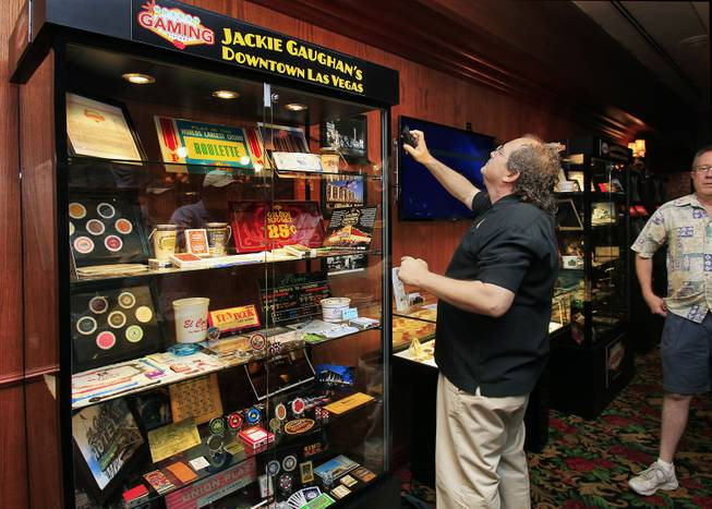 "Neal Silverman ensures the display is working during the El Cortez Hotel & Casino premiere of the Jackie Gaughan memorial exhibit titled Jackie Gaughans Downtown as seen through Gaming Memorabilia"" on Tuesday, June 17, 2014.  Silverman is a Museum of Gaming History board of director's member and helped to put the display together."