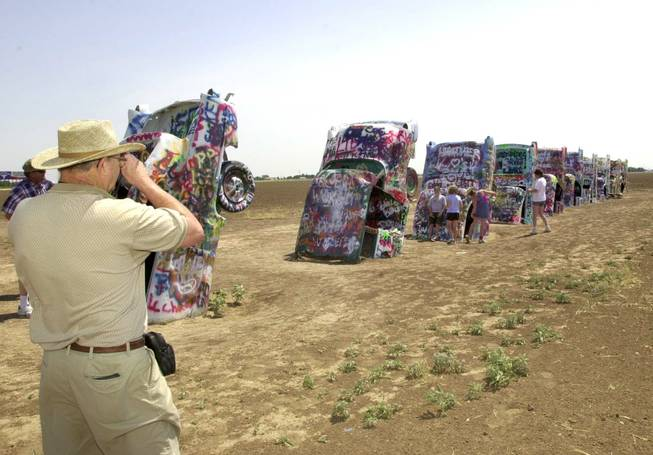 Donald Benton, left, photographs members of his family during a stop at the Cadillac Ranch just west of Amarillo, Texas, June 18, 2002.