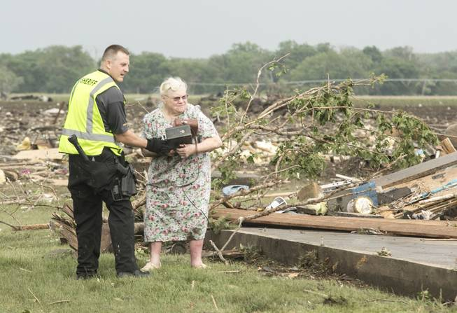 Ruth Labenz is assisted to safety by a Stanton County Sherriff's officer after her home was destroyed in the town of Pilger, Neb. Monday, June 16, 2014. At least one person is dead and at least 16 more are in critical condition after two massive tornadoes swept through northeast Nebraska on Monday.