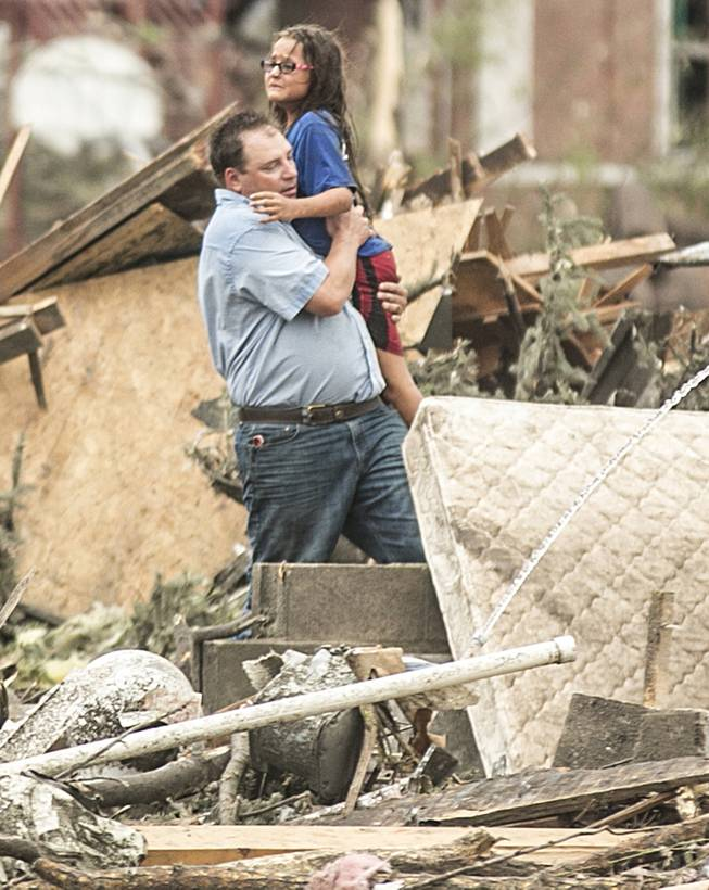 A man holds a girl after she was pulled from the basement of her destroyed home in Pilger, Neb., Monday, June 16, 2014. A hospital spokeswoman says at least one person is dead and at least 16 more are in critical condition after two massive tornadoes swept through northeast Nebraska.