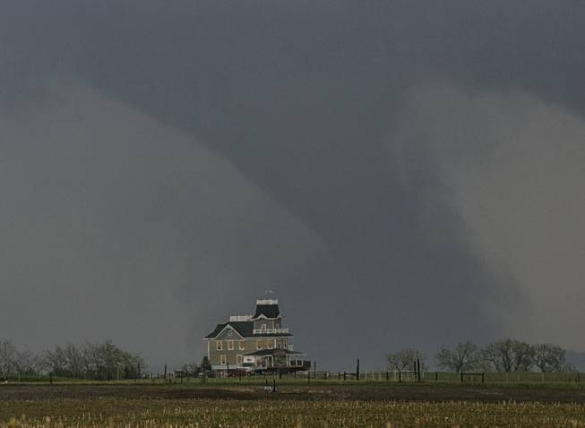 A tornado forms over a house near  Pilger, Neb., Monday, June 16, 2014. At least one person is dead and at least 16 more are in critical condition after two massive tornadoes swept through northeast Nebraska on Monday.
