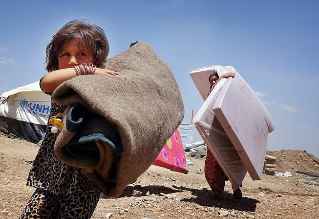 Iraqis who have fled fighting between security forces and al-Qaida inspired militants in their hometown of Tal Afar carry their belongings at Germawa camp for displaced Iraqis, in a hot dusty plain in the largely autonomous Kurdish area of Dahuk, 260 miles northwest of Baghdad, Tuesday, June 17, 2014.