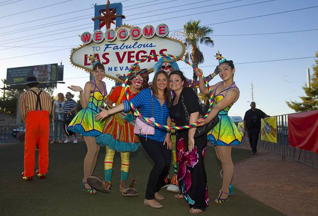 Maya Kobray, left, of New York City, and Dionne Farino of Chicago poses with members of Ringling Bros. and Barnum & Bailey Circus entertain tourists and pose for photographs at the Welcome to Fabulous Las Vegas sign Wednesday, June 18, 2014. The circus performs at Thomas & Mack Center Thursday through Sunday.