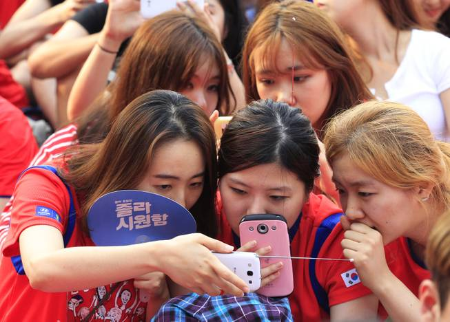 South Korean soccer fans use their smartphones to watch a live broadcast of the group H World Cup soccer match between Russia and South Korea as the screen was turned off due to a network error at a public viewing venue in Seoul, South Korea, Wednesday, June 18, 2014.(AP Photo/Ahn Young-joon)