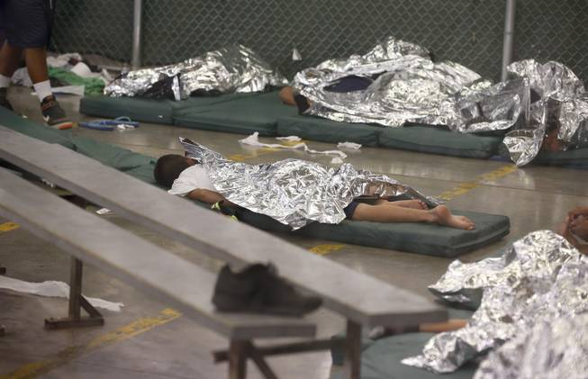 Young boys sleep in a holding cell where hundreds of mostly Central American immigrant children are being processed and held at the U.S. Customs and Border Protection Nogales Placement Center on Wednesday, June 18, 2014, in Nogales, Ariz.
