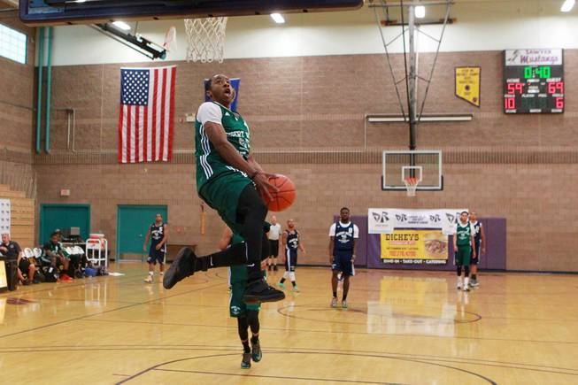 Former UNLV guard Kevin Olekaibe sails in for a fast break dunk during his Desert Reign basketball league game Wednesday, June 18, 2014.