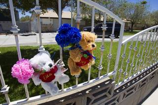Stuffed bears with the names of Ella and Cruz Flores are posted on a fence after an early morning fire at the home near Ann Road and Durango Drive Thursday, June 19, 2014. The children, ages 2 and 4-years-old, died in the fire.