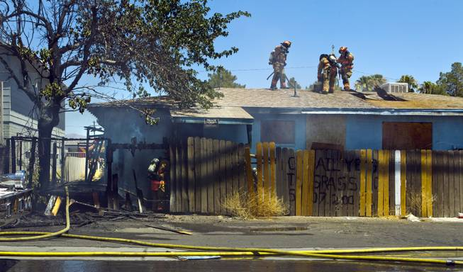 Las Vegas Fire & Rescue cut a hole in the roof during an apartment fire at 1820 East Lewis Ave. which spread to a nearby tree and shed on Thursday, June, 19, 2014.