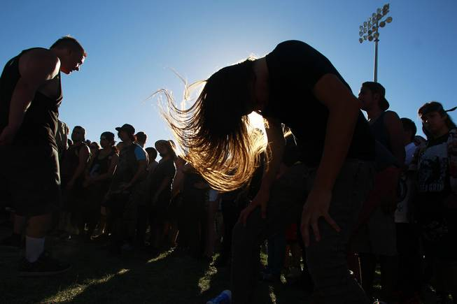 Fans headbang to the band Born of Osiris during the Las Vegas stop of the Vans Warped Tour Thursday, June 19, 2014.