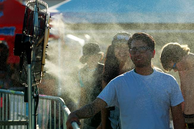 Attendees stand in misters to cool off during the Las Vegas stop of the Vans Warped Tour Thursday, June 19, 2014.