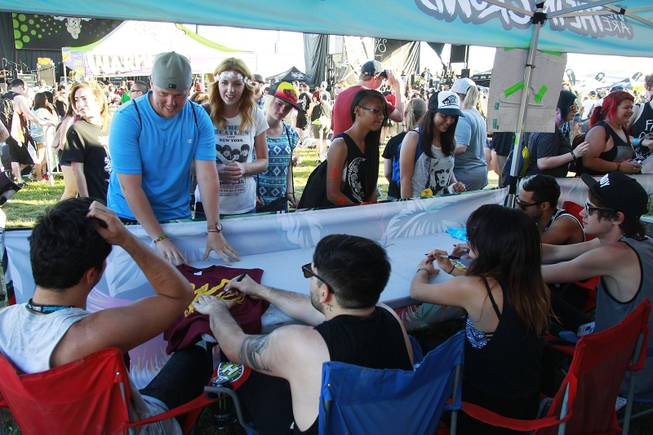 Fans line up for autographs with the band We Are the In Crowd during the Las Vegas stop of the Vans Warped Tour Thursday, June 19, 2014.