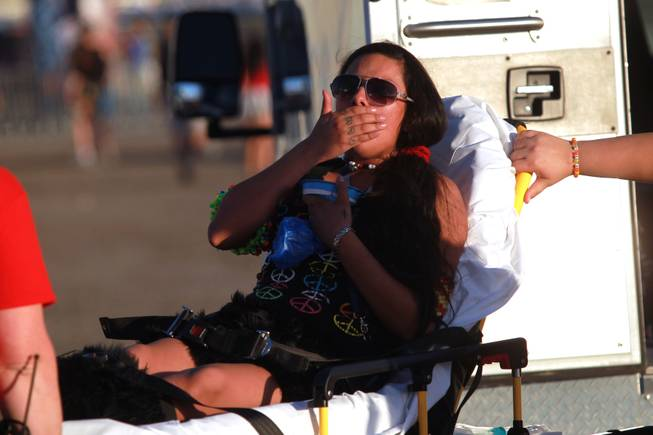 A young woman who fell ill at the entrance gate is wheeled into an ambulance during the first night of the Electric Daisy Carnival Friday, June 20, 2014 at the Las Vegas Motor Speedway.