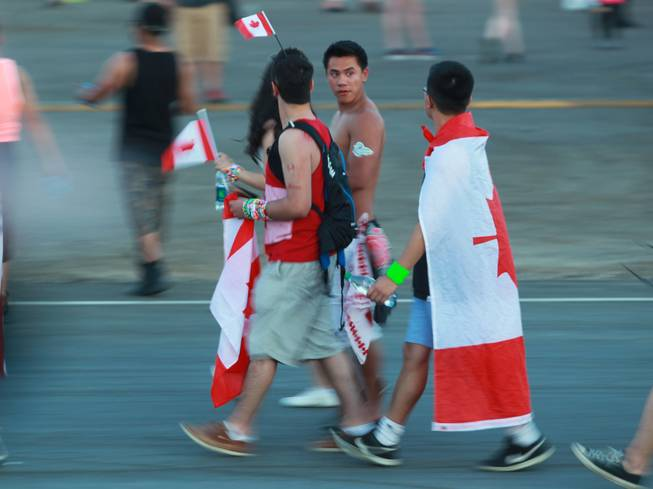 Festival goers with Canadian flags make their way to a stage during the first night of the Electric Daisy Carnival Friday, June 20, 2014 at the Las Vegas Motor Speedway.