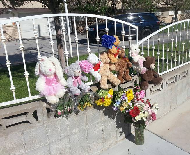 A memorial of stuffed animals and flowers is shown Thursday, June 19, 2014, at the home where two children died in an early-morning fire.