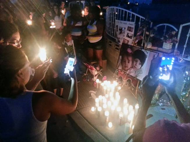 People are shown at a candlelight vigil Thursday, June 19, 2014, at the home where two children died in an early-morning fire.
