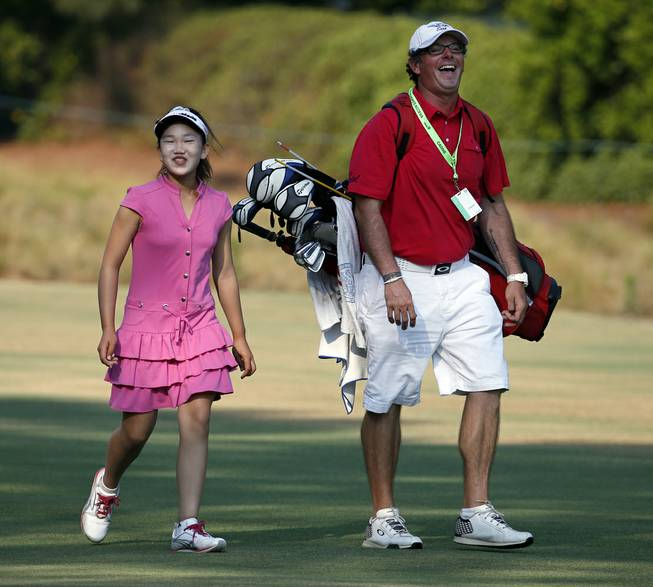 Lucy Li, left, shares a laugh with her caddy as they walk to the second green during a practice round for the U.S. Women's Open golf tournament in Pinehurst, N.C., Wednesday, June 18, 2014. The sixth-grader from California is the youngest qualifier in the history of the U.S. Women's Open.