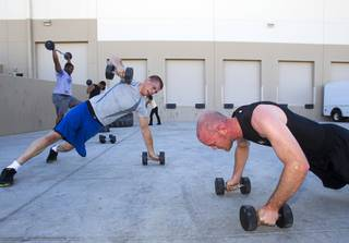 James Chaney, left, and Trevor Hall work out during a MMA bootcamp fitness class at the Syndicate MMA Gym, 6980 W Warm Springs Rd., Thursday, June 19, 2014.