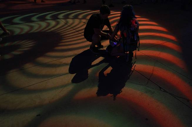 A couple crouches in a pool of light during the first night of the Electric Daisy Carnival Saturday, June 21, 2014 at the Las Vegas Motor Speedway.