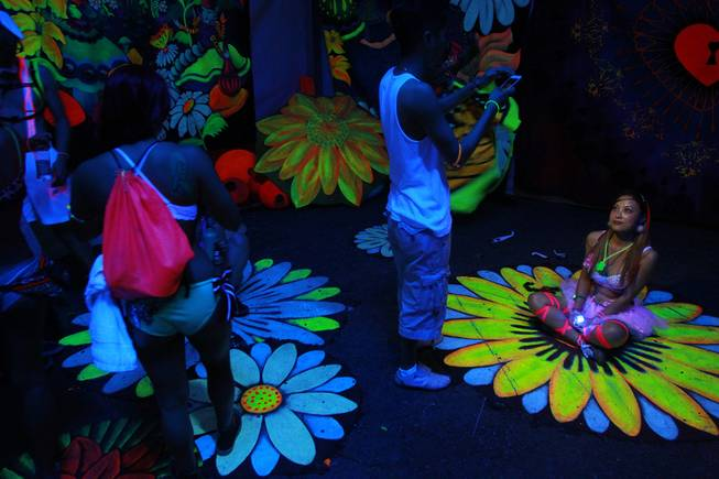 Attendees explore a black light, 3D installation during the first night of the Electric Daisy Carnival Saturday, June 21, 2014 at the Las Vegas Motor Speedway.