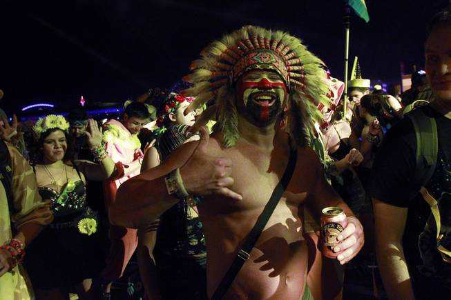 An attendee wearing a native American headdress listens to a set during the first night of the Electric Daisy Carnival Saturday, June 21, 2014 at the Las Vegas Motor Speedway.