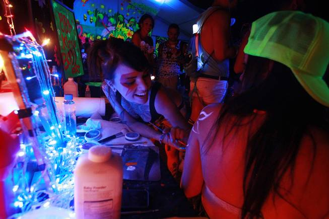 Heather Stokes from Palm Desert, Calif., paints a flower on Elizabeth Nunez from Chicago during the first night of the Electric Daisy Carnival Saturday, June 21, 2014 at the Las Vegas Motor Speedway.