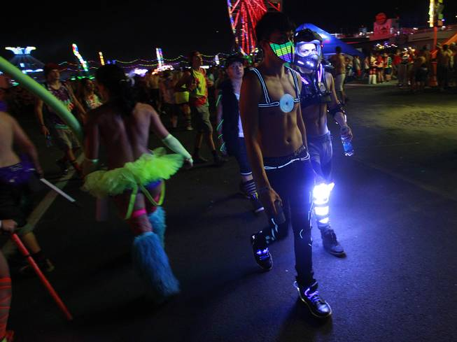 Attendees in costume walk the grounds during the first night of the Electric Daisy Carnival Saturday, June 21, 2014 at the Las Vegas Motor Speedway.