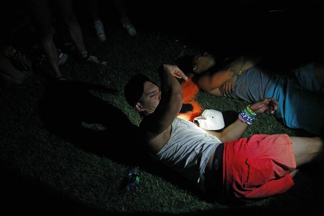 A beam from a security guard's flashlight awakens a sleeping person during the first night of the Electric Daisy Carnival early Saturday, June 21, 2014 at the Las Vegas Motor Speedway.