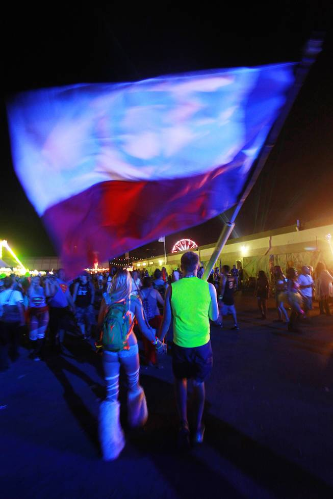 A couple carry a large flag during the first night of the Electric Daisy Carnival early Saturday, June 21, 2014 at the Las Vegas Motor Speedway.