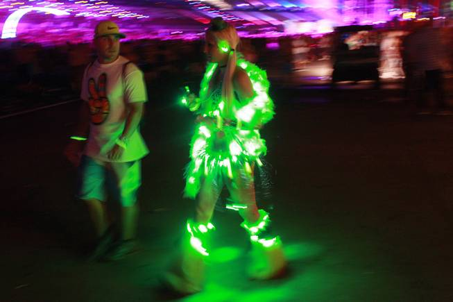 A woman festooned in lights walks with a young man during the first night of the Electric Daisy Carnival early Saturday, June 21, 2014 at the Las Vegas Motor Speedway.