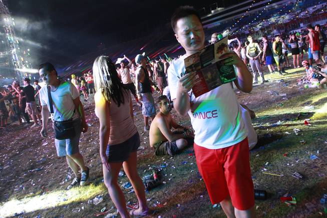 An attendee checks the schedule during the first night of the Electric Daisy Carnival early Saturday, June 21, 2014 at the Las Vegas Motor Speedway.