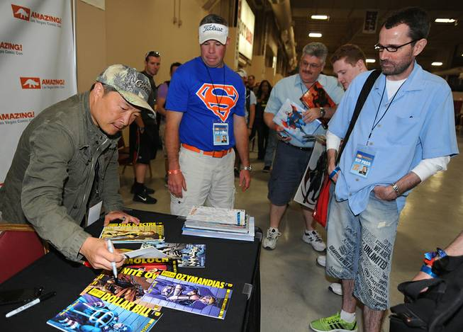 Comic book artist Jim Lee autographs items for fans during the first day of Las Vegas Comic Con 2014 at the South Point Convention Center on Saturday, June 21, 2014.