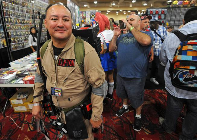 "Michael Clifton, of Nellis Air Force Base, poses as a Ghostbuster while a fan photographs his ""proton pack"" during the first day of the Las Vegas Comic Con at the South Point Convention Center on Saturday, June 21, 2014."