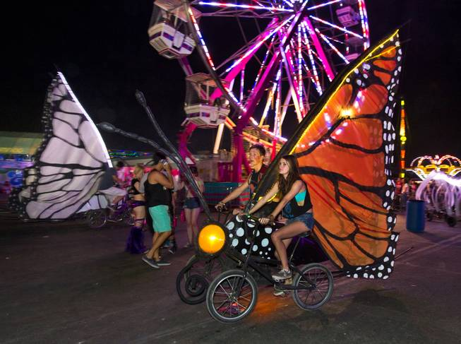 Butterfly bicycles are pedaled along the concourse during opening night of EDC at the Las Vegas Motor Speedway on Friday, June 20, 2014.