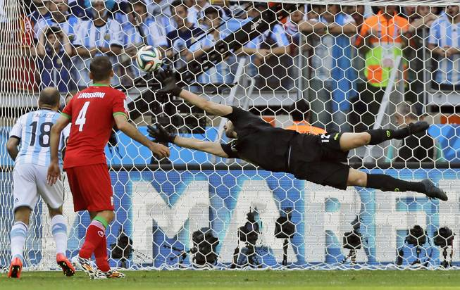 Argentina's Rodrigo Palacio and Iran's Jalal Hosseini watch as Iran's goalkeeper Alireza Haghighi dives but allows a goal by Argentina's Lionel Messi during a World Cup soccer match at the Mineirao Stadium in Belo Horizonte, Brazil, on Saturday, June 21, 2014. Argentina defeated Iran 1-0.