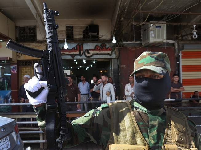 An Iraqi Shiite masked militiaman, a follower of Shiite cleric Muqtada al-Sadr, holds up his machine gun during a parade in the northern oil rich province of Kirkuk, Iraq, on Saturday, June 21, 2014. Thousands of heavily-armed Shiite militiamen paraded through several Iraqi cities on Saturday as Sunni militants seized two strategically located towns in what appeared to be a new offensive in the western Anbar province.