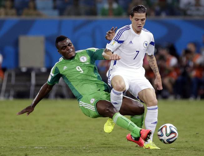 Nigeria's Emmanuel Emenike slides into Bosnia-Herzegovina's Muhamed Besic to kick the ball away during the a World Cup soccer match at the Arena Pantanal in Cuiaba, Brazil, on Saturday, June 21, 2014.