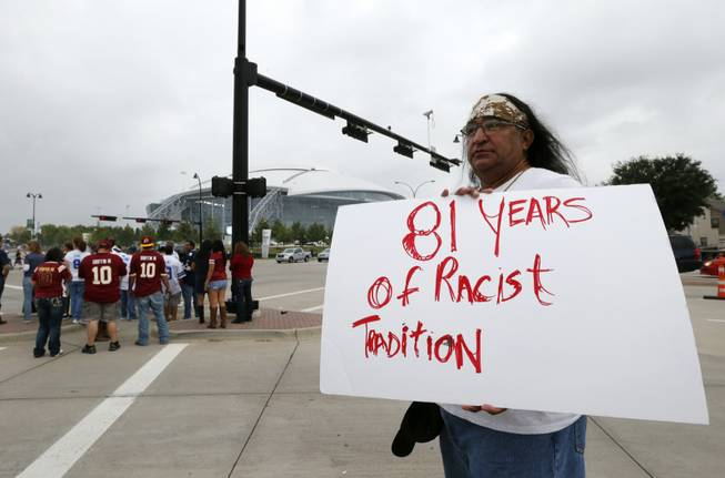 "In this Oct. 13, 2014, file photo, Juan Mancias, of Floresville, Texas, a member of the American Indian Movement of Central Texas, holds a sign as he joins others in protest before an NFL football game between the Washington Redskins and Dallas Cowboys in Arlington, Texas. The U.S. Patent Office ruled Wednesday, June 18, 2014, that the Washington Redskins nickname is ""disparaging of Native Americans"" and that the team's federal trademarks for the name must be canceled."