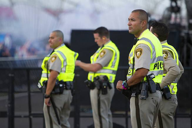 Metro Police Officer Rico Rodriguez, right, keeps watches music fans during the final day of the 2014 Electric Daisy Carnival (EDC) at the Las Vegas Motor Speedway Sunday, June 22, 2014.