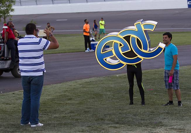Michael Haro of Mexico has his photo taken with a human EDC sign during the final day of the 2014 Electric Daisy Carnival (EDC) at the Las Vegas Motor Speedway Sunday, June 22, 2014.