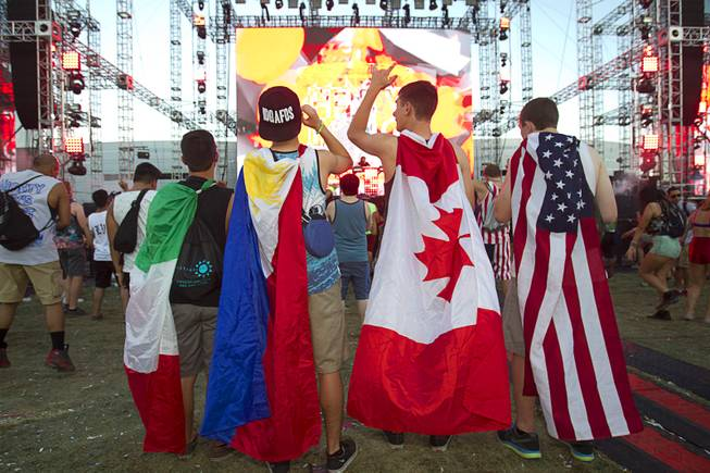 Fans with flags, representing from left, Mexico, Philippines, Canada and the USA, listen to music by Henry Fong during the final day of the 2014 Electric Daisy Carnival (EDC) at the Las Vegas Motor Speedway Sunday, June 22, 2014.