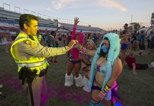 Jackie Aguilar of California gives a bracelet to Metro Police Sgt. David Schofield during the final day of the 2014 Electric Daisy Carnival (EDC) at the Las Vegas Motor Speedway Sunday, June 22, 2014.