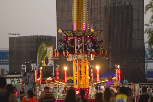 Music fans take a carnival ride during the final day of the 2014 Electric Daisy Carnival (EDC) at the Las Vegas Motor Speedway Sunday, June 22, 2014.