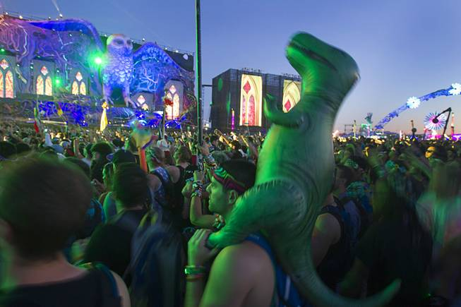 A man and his inflatable dinosaur are shown during the final day of the 2014 Electric Daisy Carnival (EDC) at the Las Vegas Motor Speedway Sunday, June 22, 2014.